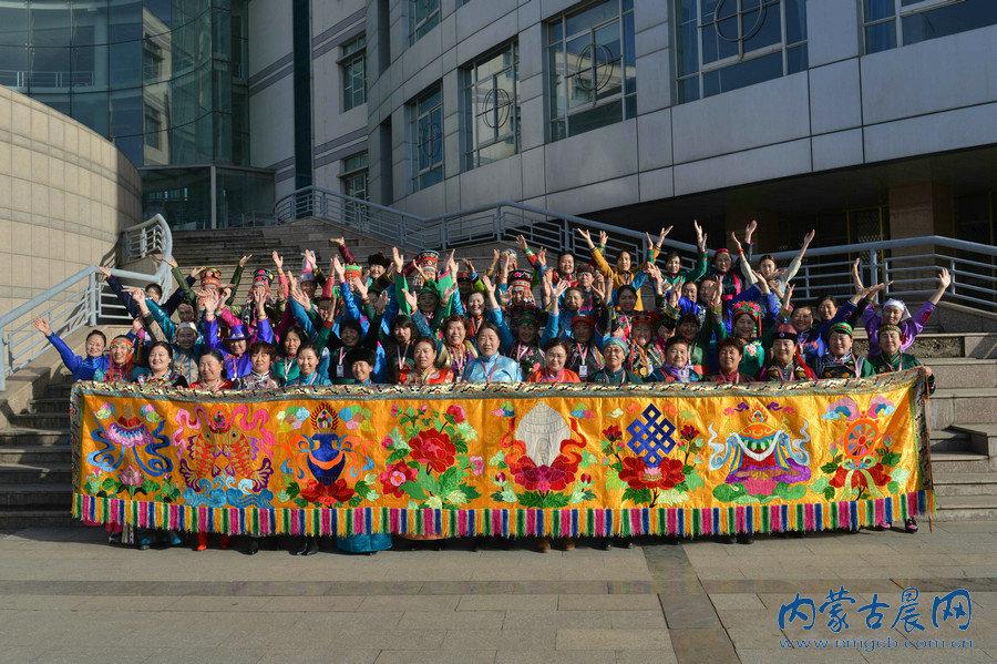 传承人集体展示哈斯琪琪格(前排中)创作的蒙古族刺绣巨幅作品《吉祥八宝》。